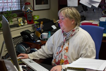 Associate Dean of the College of Arts and Sciences Neva Specht looks over work in her office. Photo by Dallas Linger  |  The Appalachian