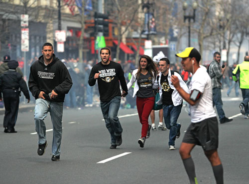 Spectators flee from the scene of the first of two explosions that shook the finish line of the 117th Boston Marathon near Copley Square on Monday afternoon. The bombings left three dead and 140 injured as of press time. Kenshin Okubo | Daily Free Press