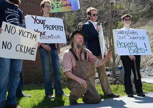 Owner of Turtle Island Preserve, Eustace Conway, speaks in front of the Watauga County Health Department surrounded by a group of supporters. A group of community members and students organized the march, which began at Sanford Mall. Olivia Wilkes | The Appalachian