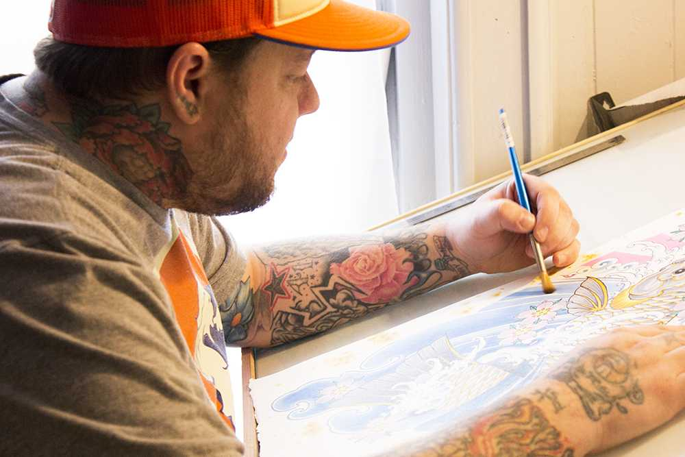Greg Kinammon working on a painting in his new tattoo studio, part of Speakeasy Tattoo Co. on Friday afternoon. His new stuido is located on Kings Street near Capones. Photo by Halle Keighton  |  The Appalachian
