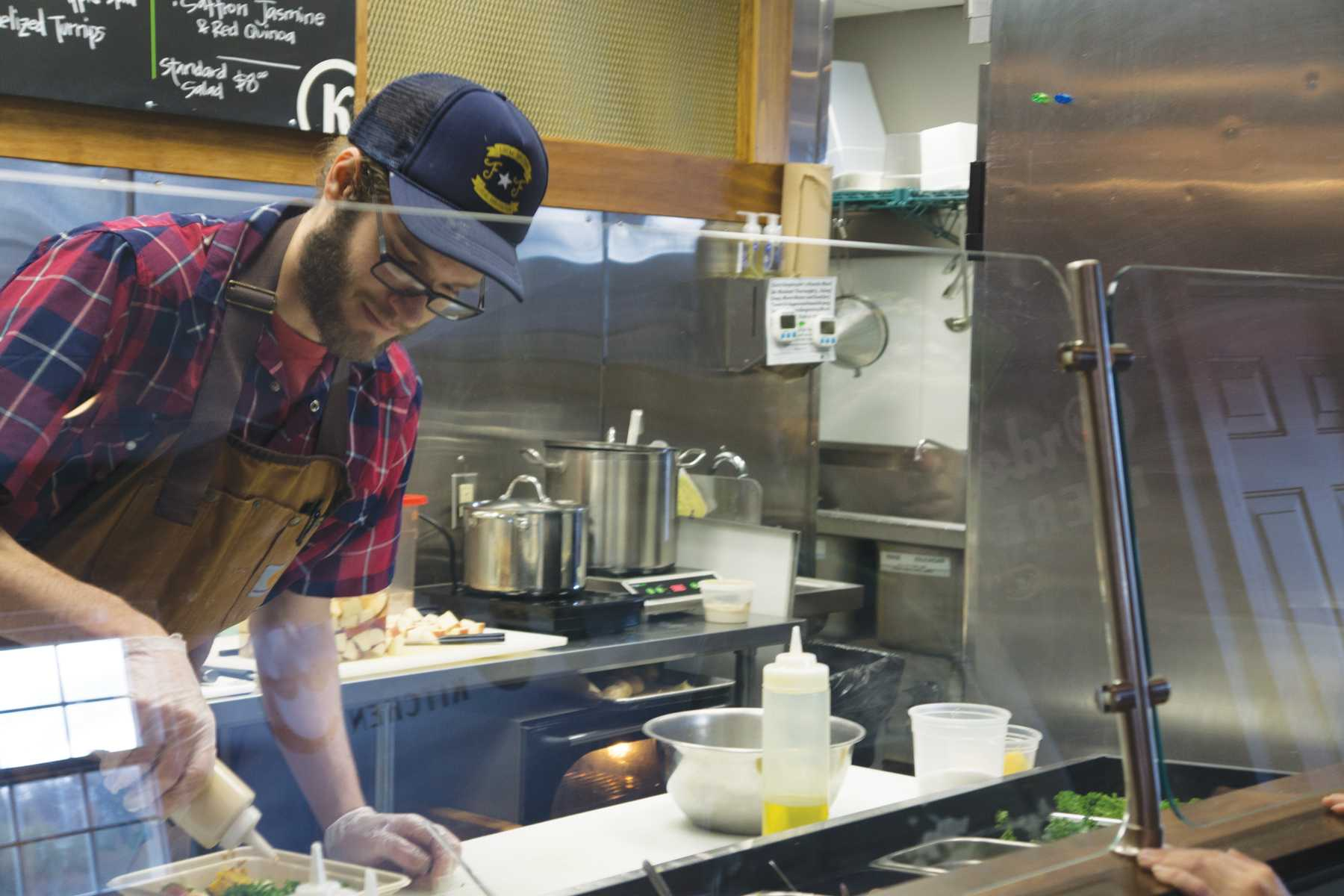 Will Crowell prepares one of Kindly Kitchen's made-to-order bowls. All food served is plant based and locally sourced.