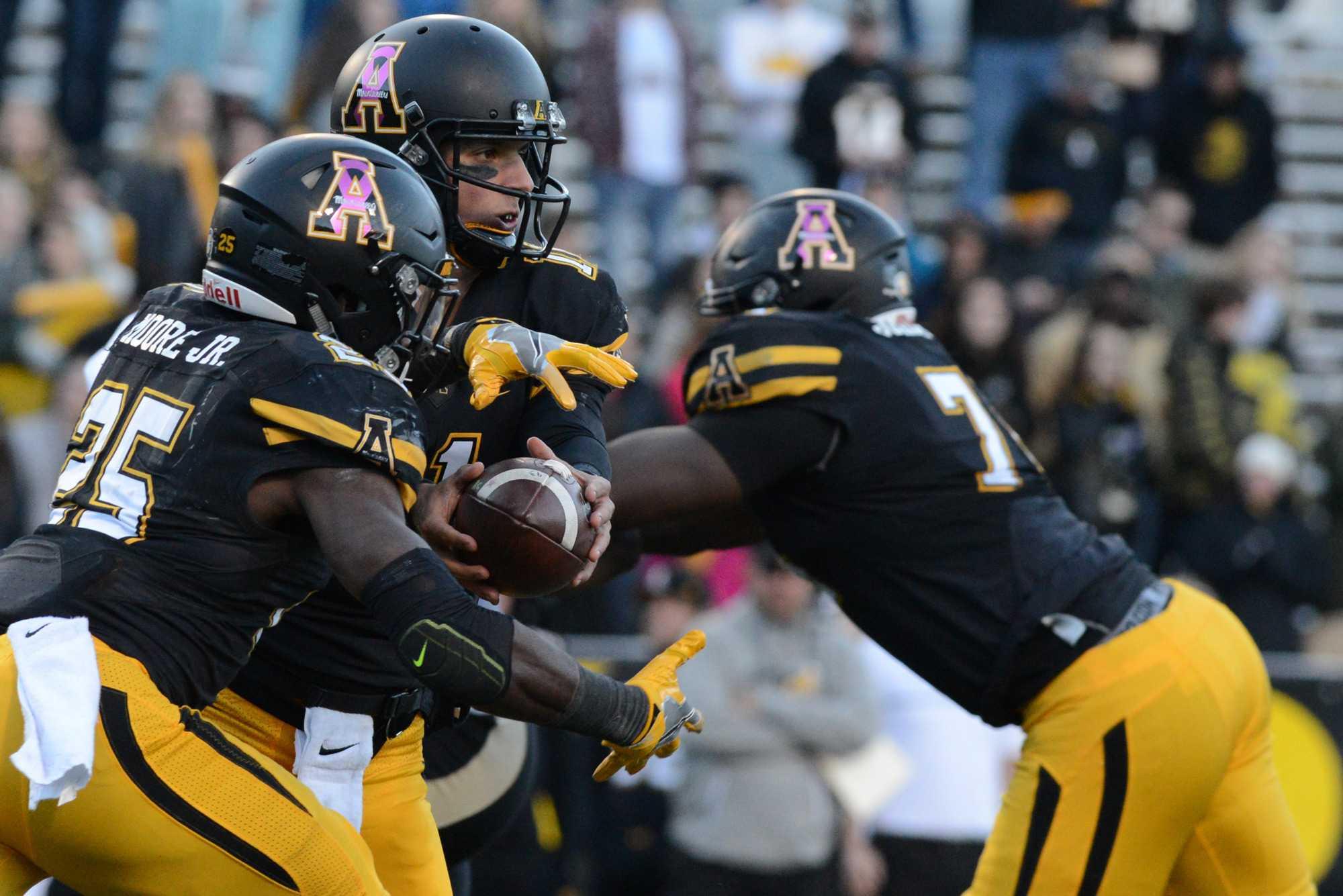 Junior quarterback Taylor Lamb hands the ball off to Sophomore running back Jalin Moore.