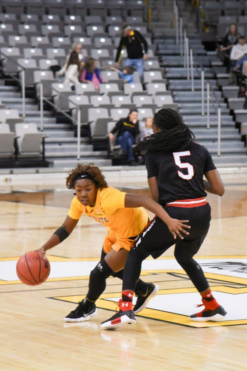 Freshman+guard+Tierra+Wilson+makes+her+way+around+an+opposing+Davidson+player+towards+the+basket.+
