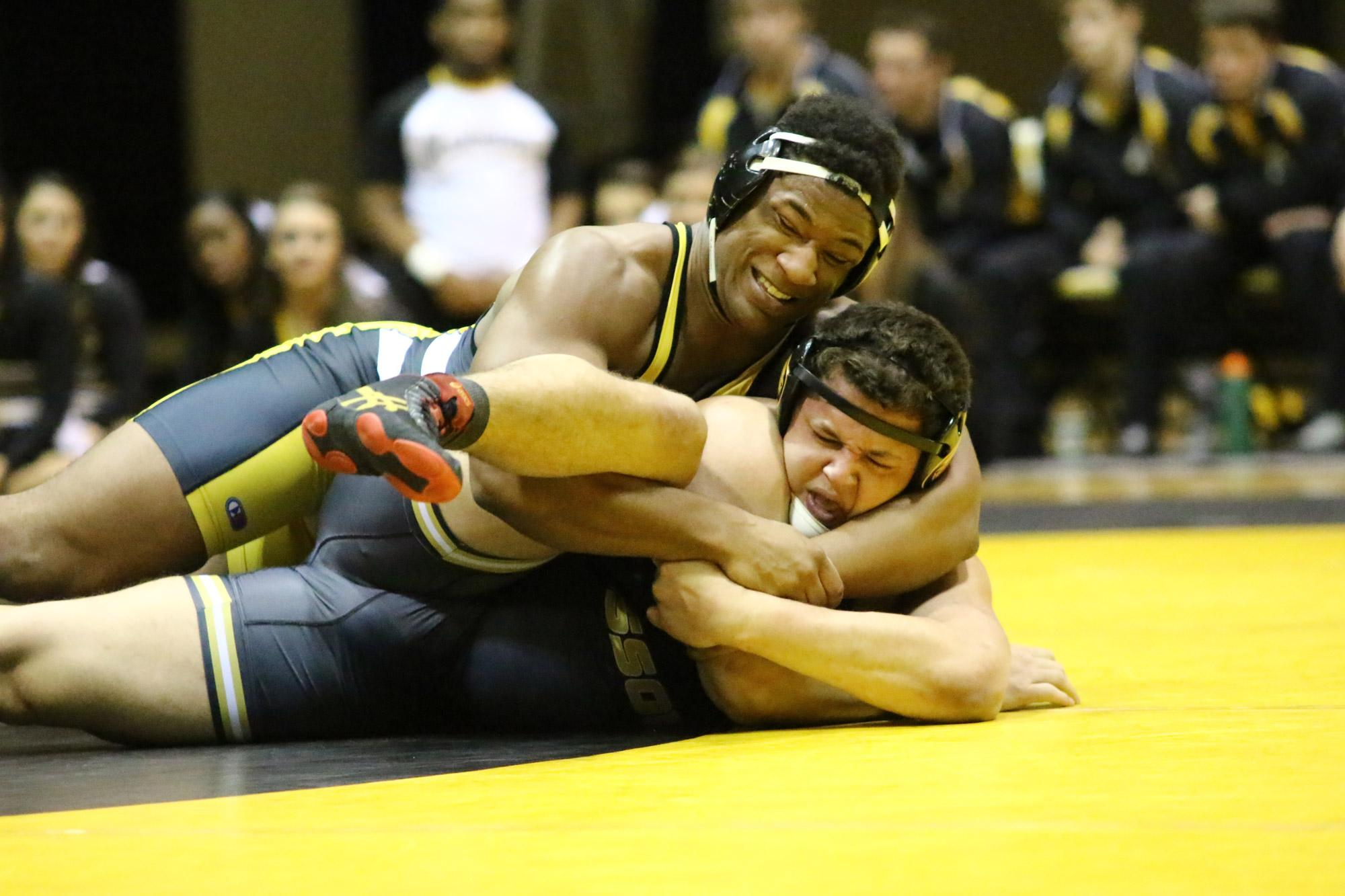 Denzel Dejournette attempts to pin his opponent during a wrestling match this season. Photo courtesy of Rob Moore.