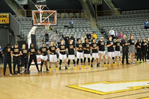 Appalachian State Women's Basketball team lines up for the National Anthem. The team is wearing their t-shirts to show support for their Coach Angel Elderkin who was diagnosed with cancer.