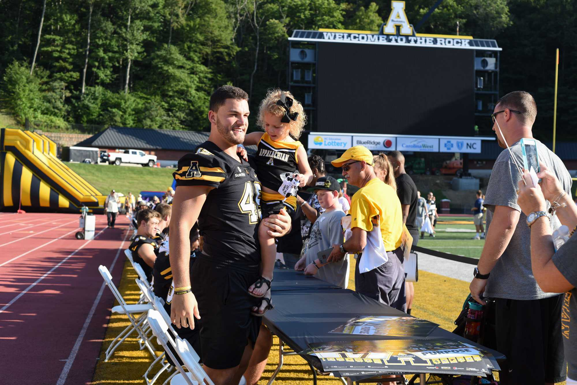 Inside linebacker Eric Boggs takes a picture with a young fan at Fan Fest. Kidd Brewer Stadium  was open to the public on Saturday for fans to come and meet their favorite App State players.