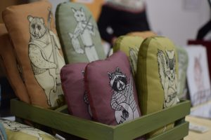 Handmade pillows for sale at the Siamese Bean table in the Handmade Market during the Fiddler's Convention.