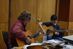 Renowned guitar maker Wayne Henderson jamming with a young guitarist at the luthiers' gathering.