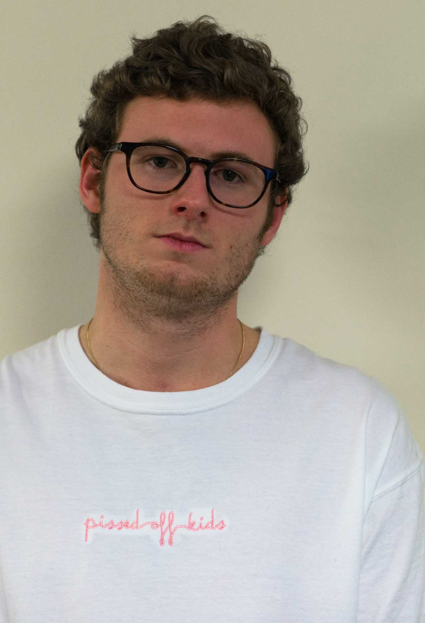 Senior communication/journalism major Hunter Greer wears a white Pissed Off Kids t-shirt. Pissed Off Kids t-shirts come in white, pink, blue and black, all with pink stitching.