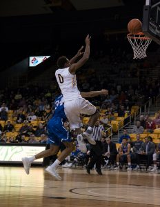 Freshman forward Isaac Johnson attempts to score with a layup during the game against UTA.