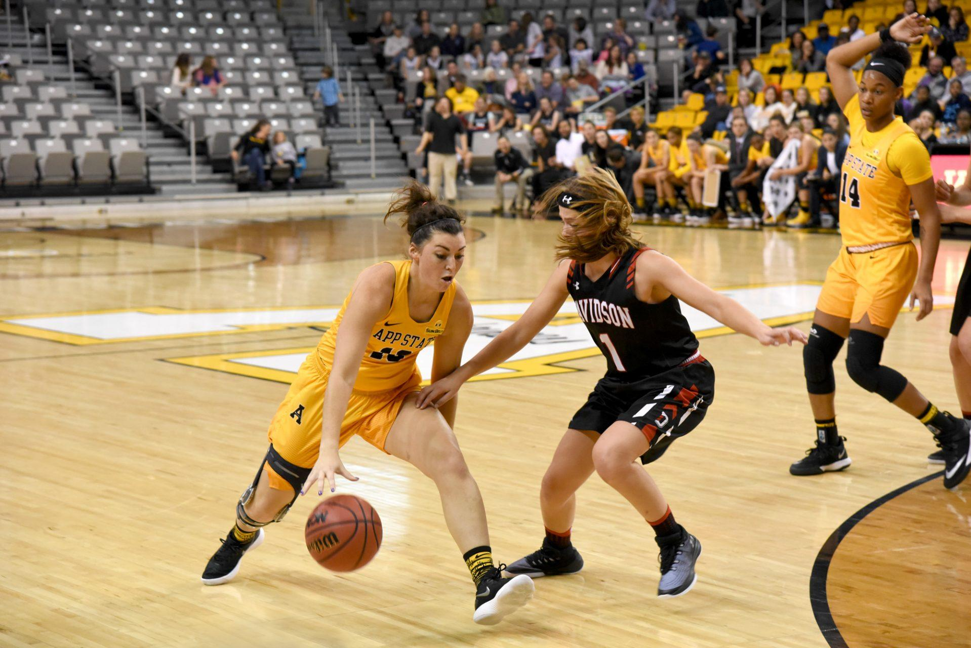 Sophomore guard Kaila Craven dribbling the ball around a player from Davidson and towards the basket On Sunday, November 19th. The Mountaineers lost the game with the final score being 59-57.