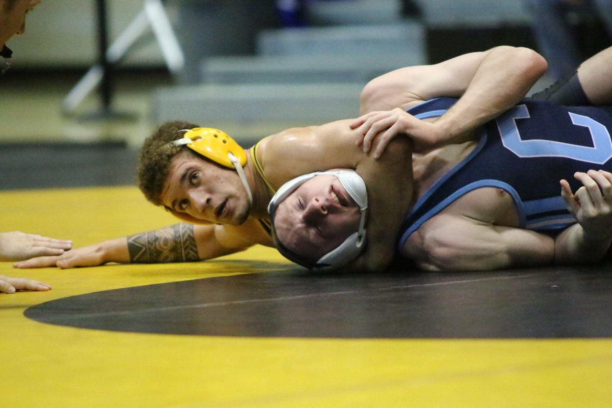 Junior Nick Kee pins his opponent down during a home match.