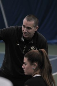 Women's Tennis Head Coach Blake Mosley gives some pointers during a match.