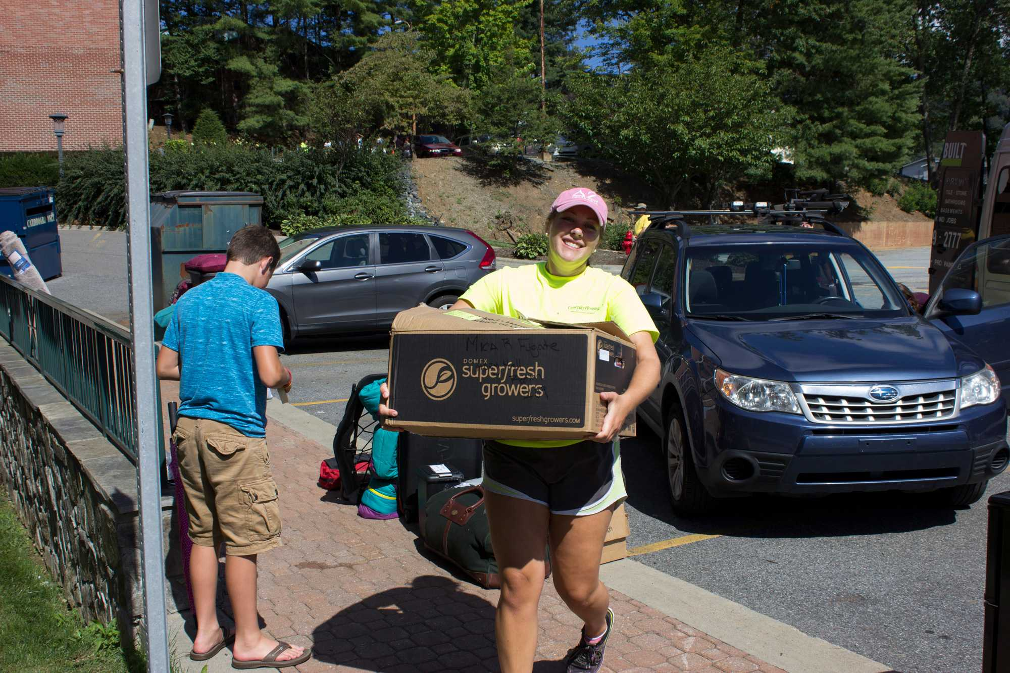 Student volunteer, Rachel Peterson, junior, helps a freshman move boxes into their room in Hoey Hall. The town of Boone was busy Friday morning as the freshman rolled into town with their parents to move into the dorms for the new school year. Photo by Halle Keighton