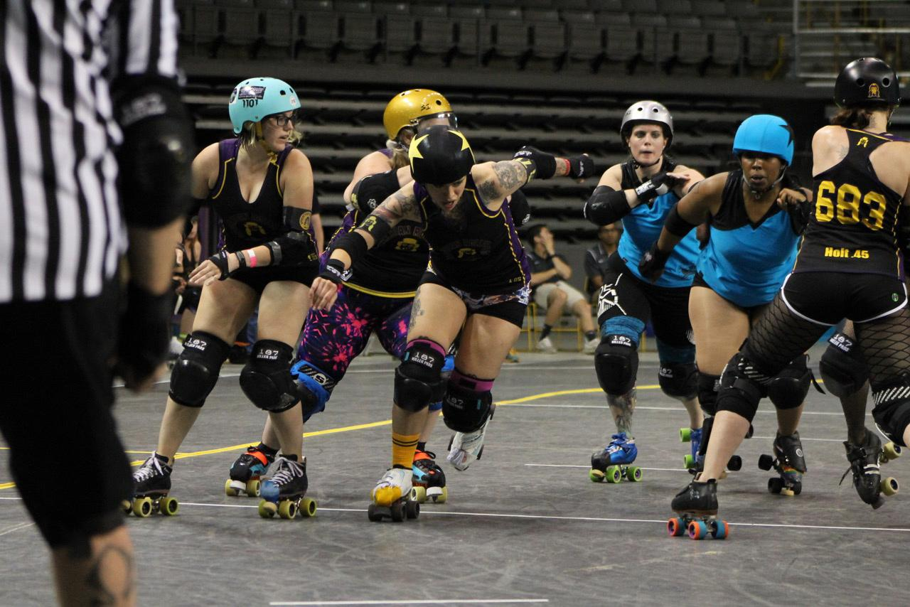 Jammer+P.Y.T.%2C+with+the+help+of+blockers+Nerfighter+aka+Amber+Williams%2C+Tutu+LaRue+aka+Billie+Jo+Burns+and+Holt+.45+aka+Sarah+Holt%2C+skates+by+pack+of+Dominion+Derby+girls+to+become+lead+jammer.+Photo+courtesy+of+Kevin+Gordon.