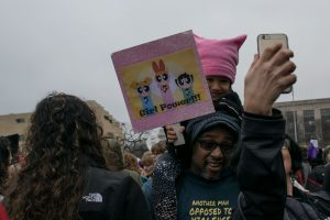 A family taking a selfie before the Women's March begins. The march was on January 21st, the day after the inauguration of President Donald Trump
