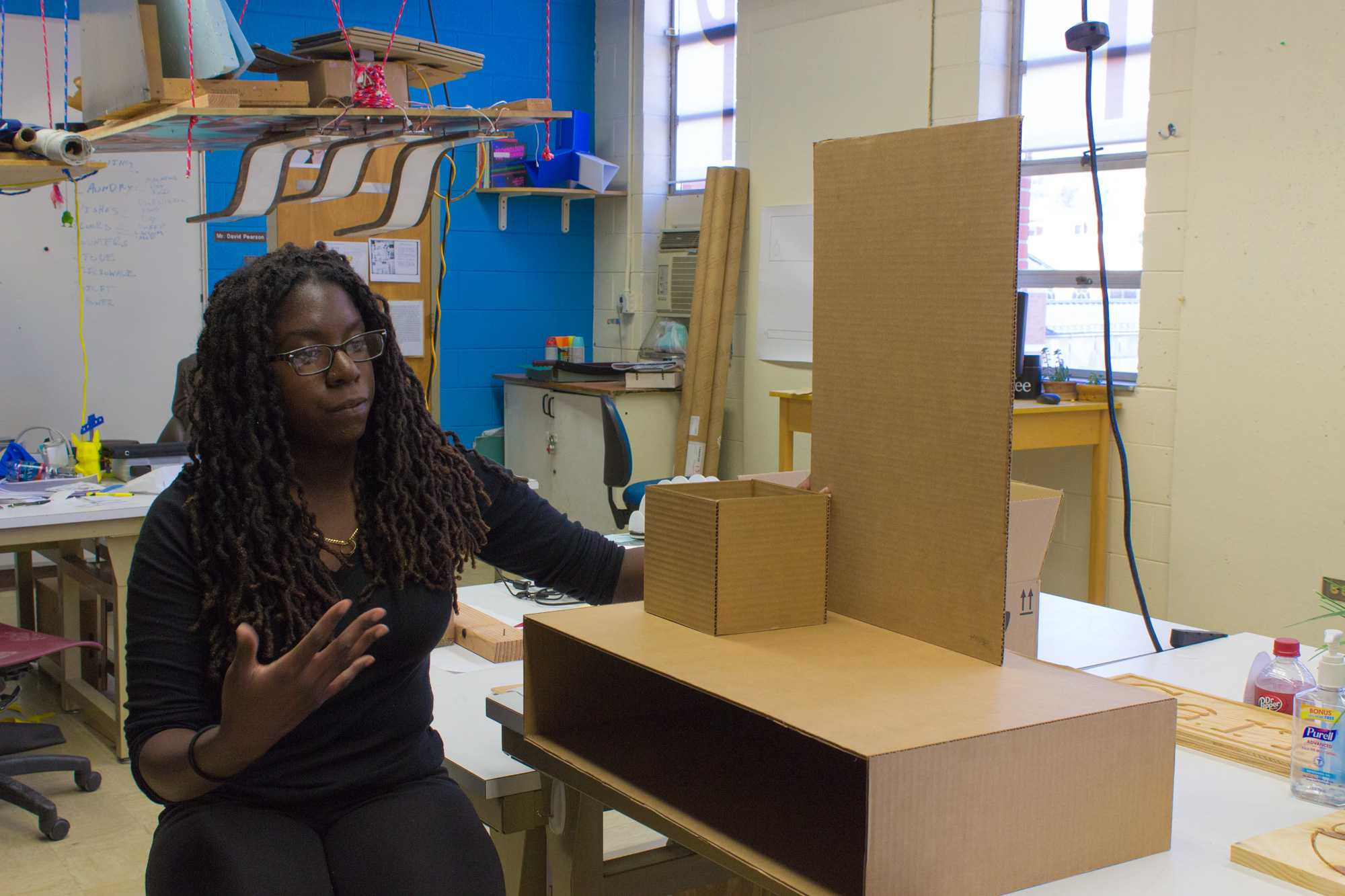 Senior industrial design major Sheilla Sanon explains her capstone project. The cardboard is a model for a shelf with a drawer, box and mirror. She describes it as a character furniture piece that describes her and her brother. Photo by Dallas Linger, Photo Editor