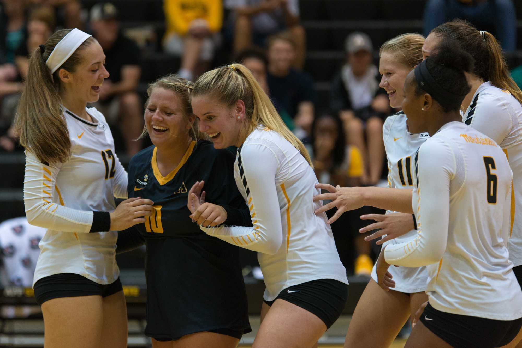 Libero/Defensive Specialist Olivia Loeffler stands up with the help of her teammates after falling and being stepped on during a play. The gold team won 4-0. Photo by Dallas Linger, Photo Editor