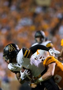 Cox is tackled by defenders while rushing with the ball.