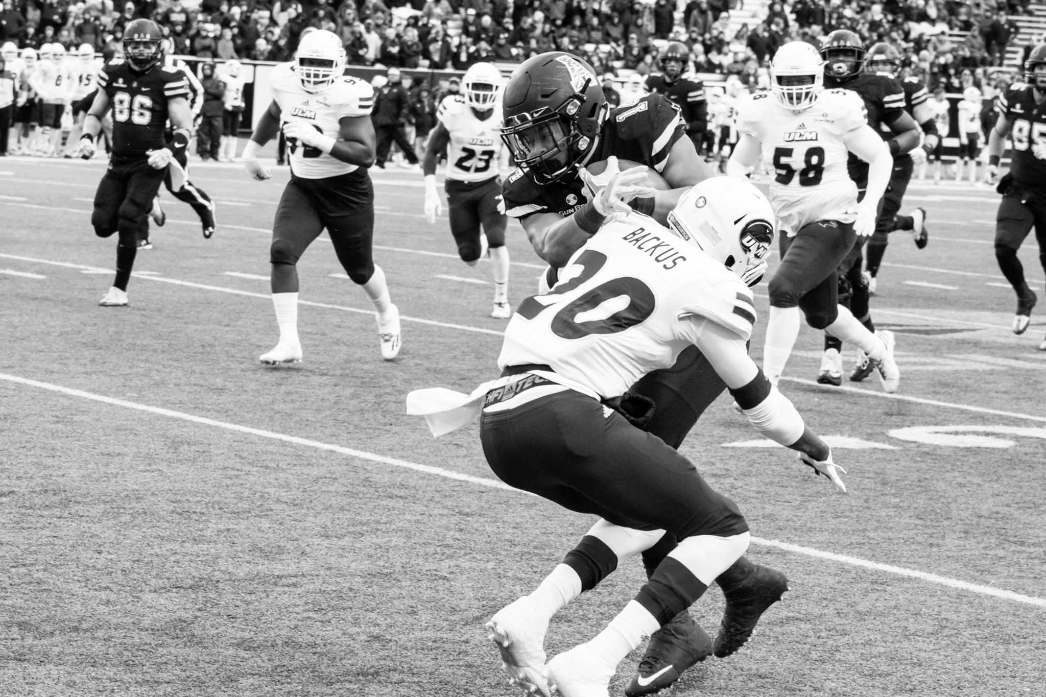 Senior running back Marcus Cox, attempts to run the ball down the field and gets tackled by the opposing team during the game against UL Monroe.