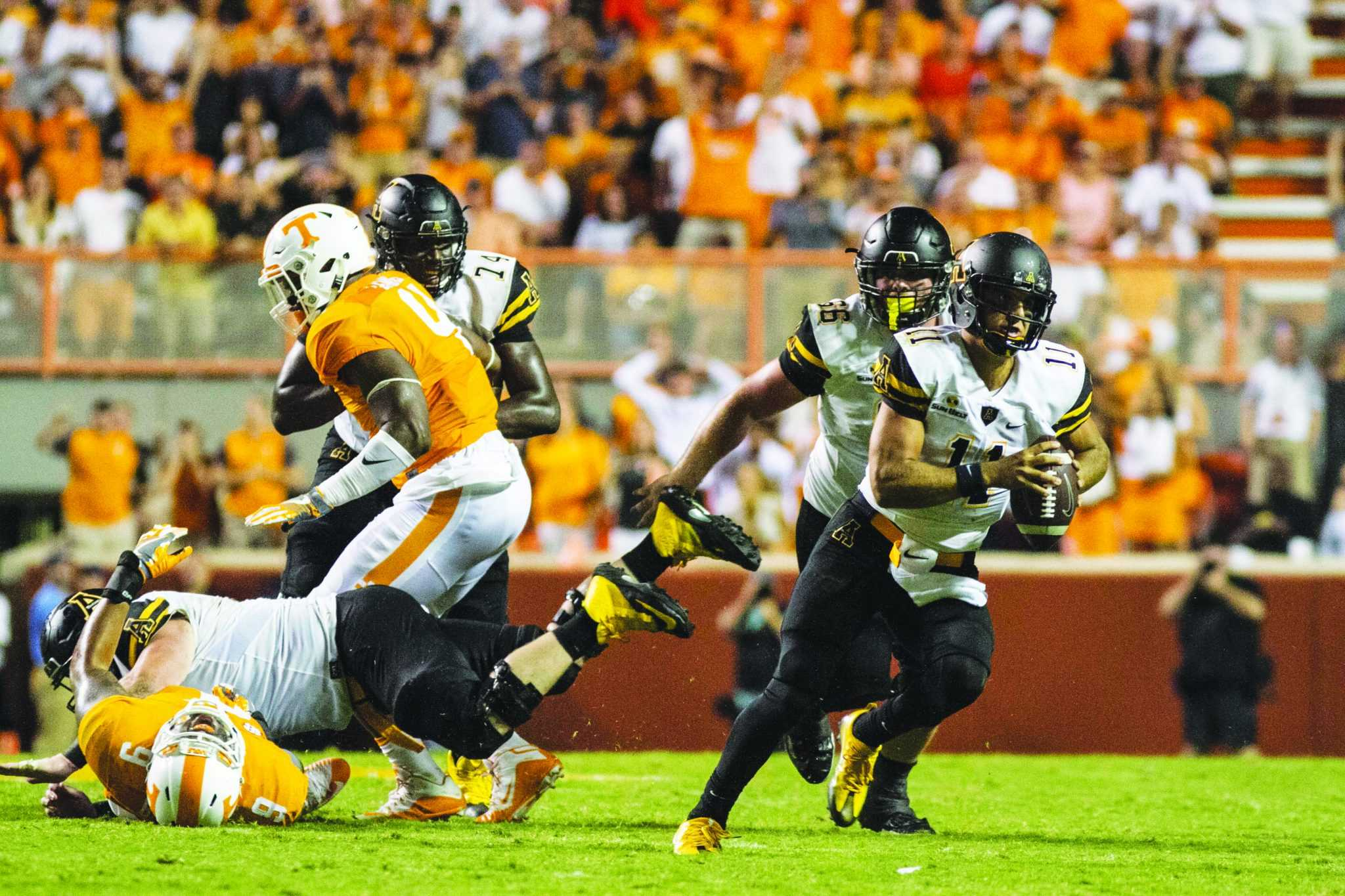 Junior Quarterback, Taylor Lamb, leads the offensive play by running the ball down the field during the Thursday night game against Tennessee. The Mountaineers lost the away game in overtime with the final score being 20-13.