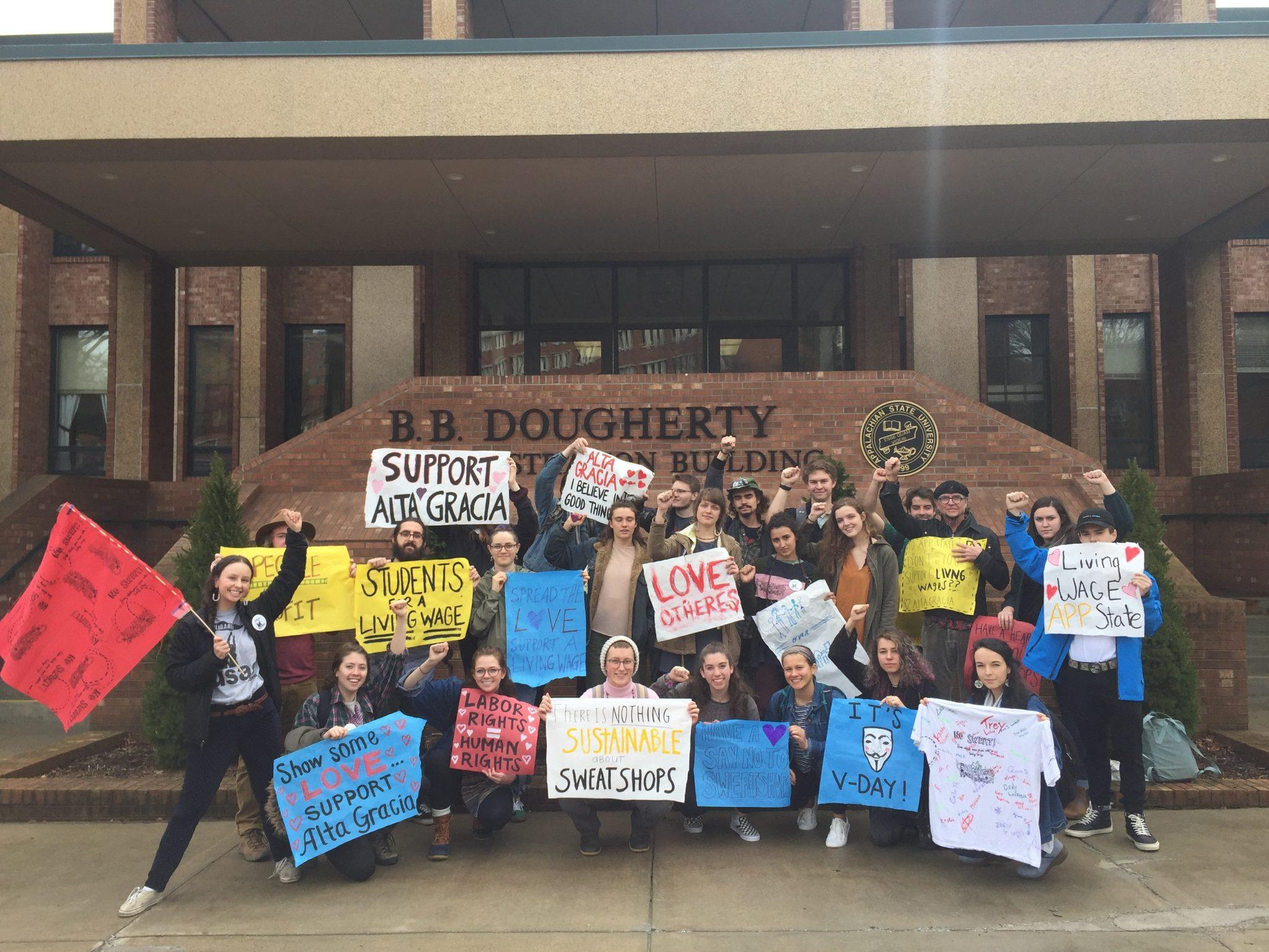 Members of USAS pose with painted signs and banners promoting Alta Gracia outside of B.B. Dougherty, where the chancellor's office is located.