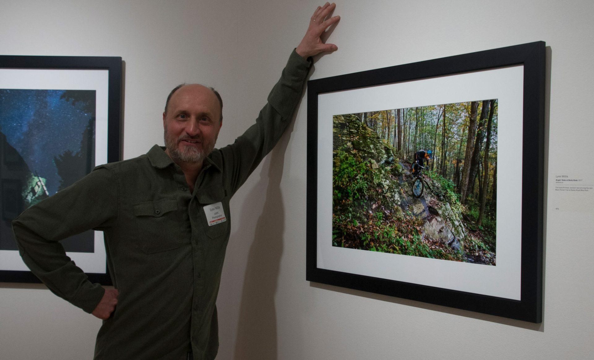 Photographer Lynn Willis stands next to his photograph titled