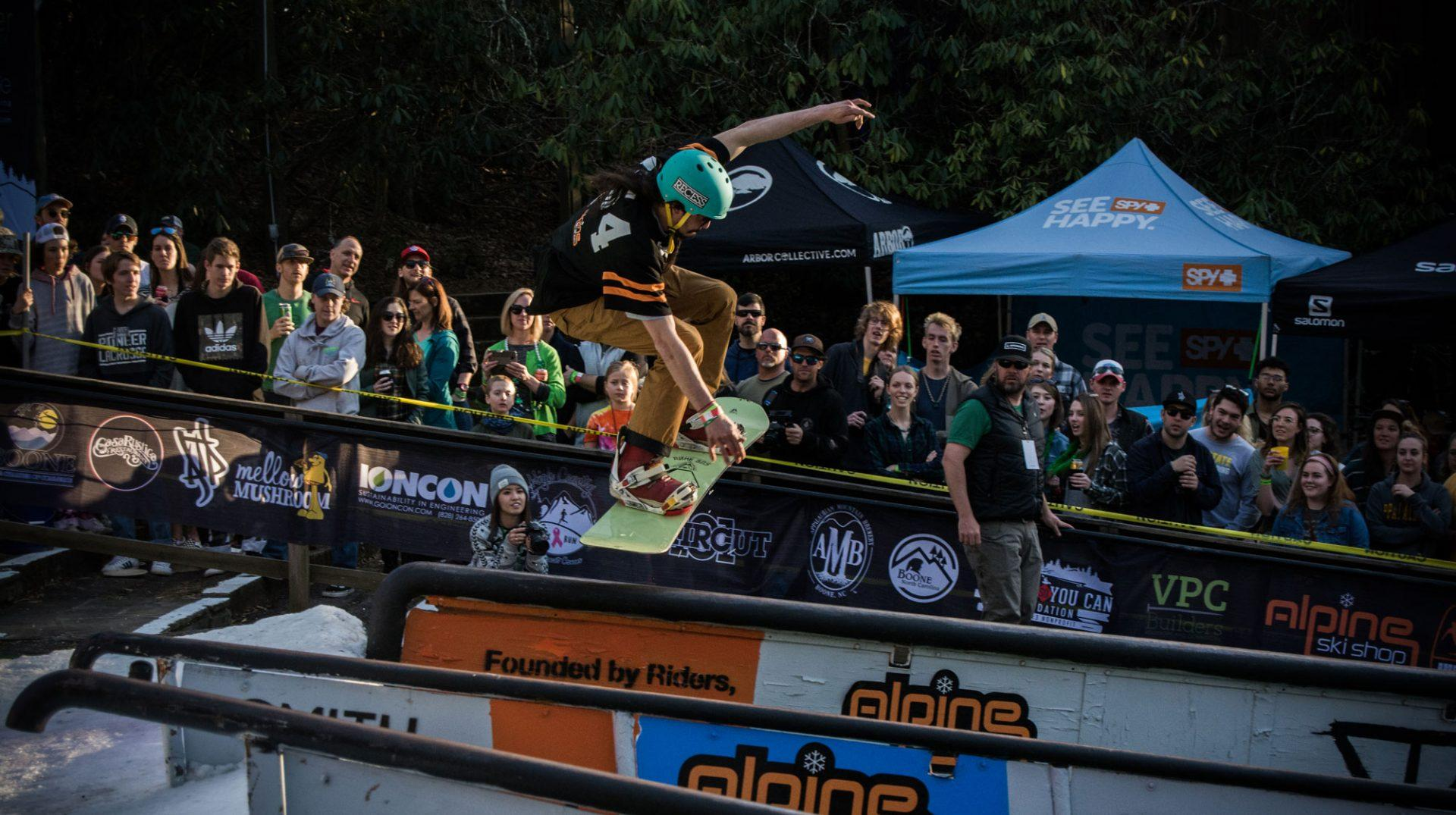 One of the competitors of Rail Jam jumping in order to boardslide a rail.