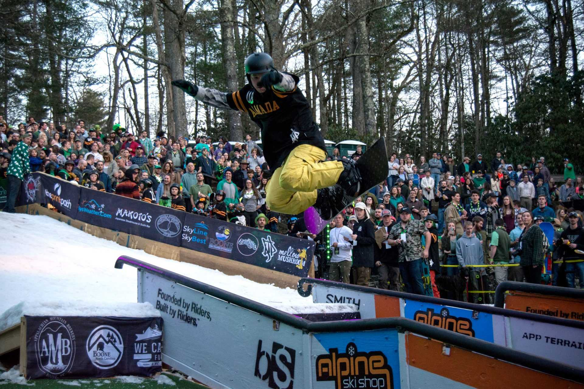 A snowboarder at Rail Jam leaps into the air off the ramp of the slope