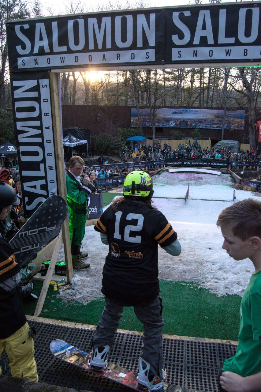 A snowboarder prepares to drop into the Rail Jam slope.