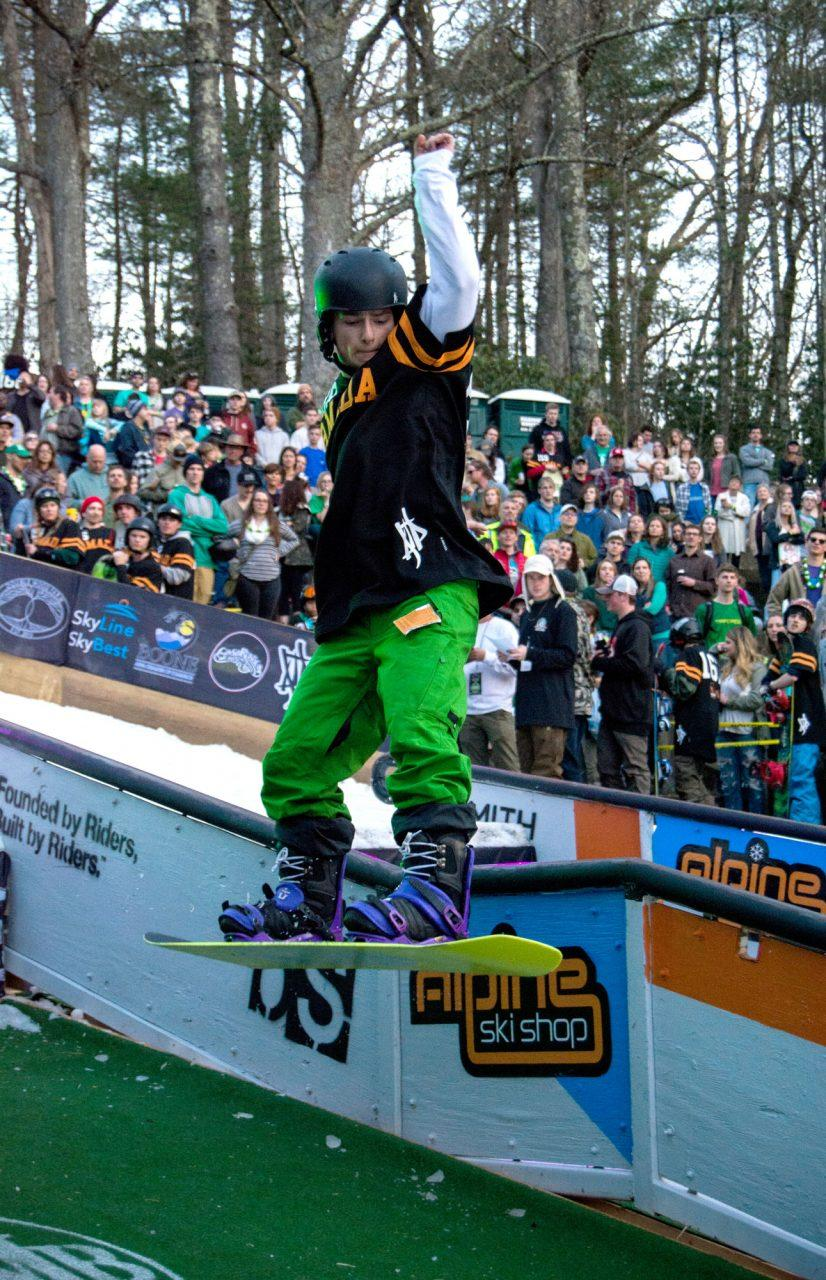 A snowboarder competing in Rail Jam comes out of a grind and prepares to land.