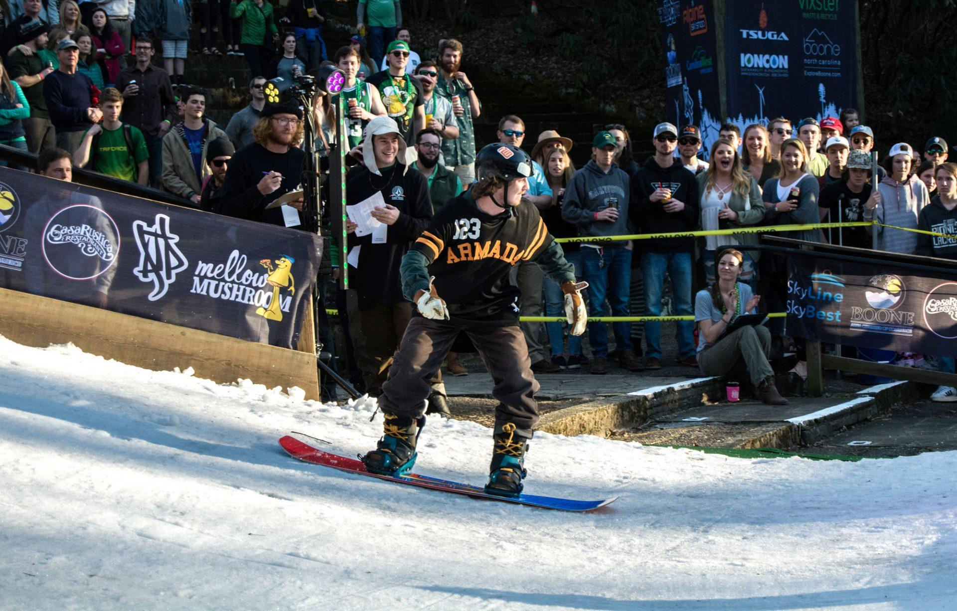 A snowboarder speeds down the slope and prepares to jump.