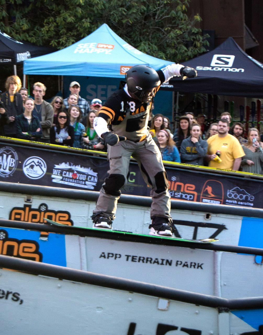 A snowboarder hits a 50-50 grind on the middle rail at the Rail Jam slope.