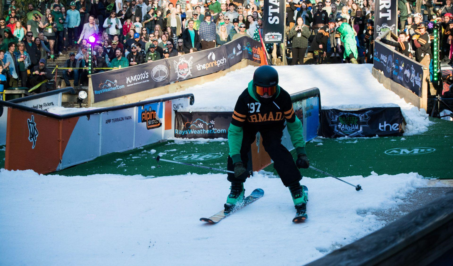 A skier zooms down the slope after landing their grind at Rail Jam on St. Patrick's Day.