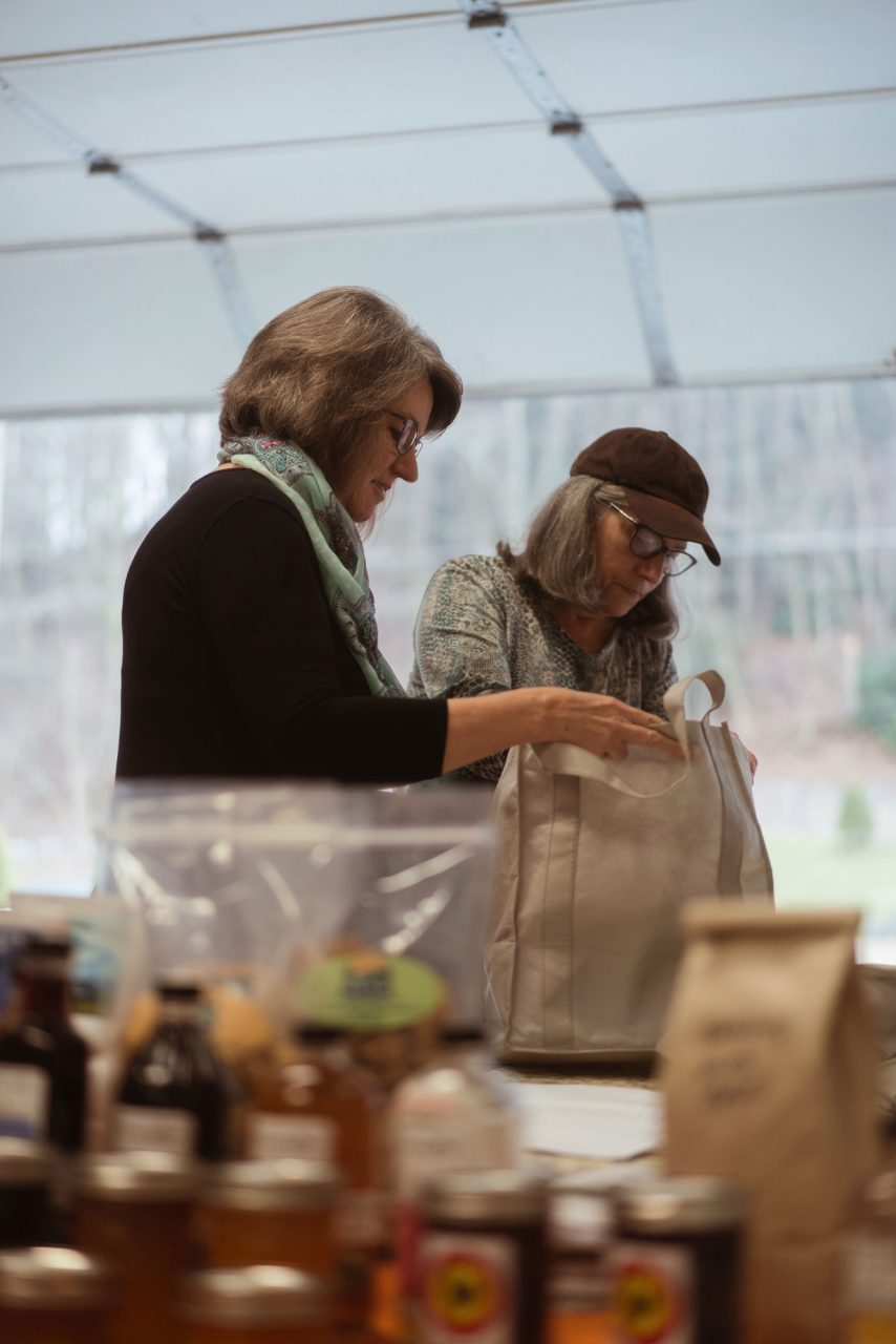 Shannon Carroll, the High Country Food Hub director, helps a customer bag her weekly purchase of local goods.
