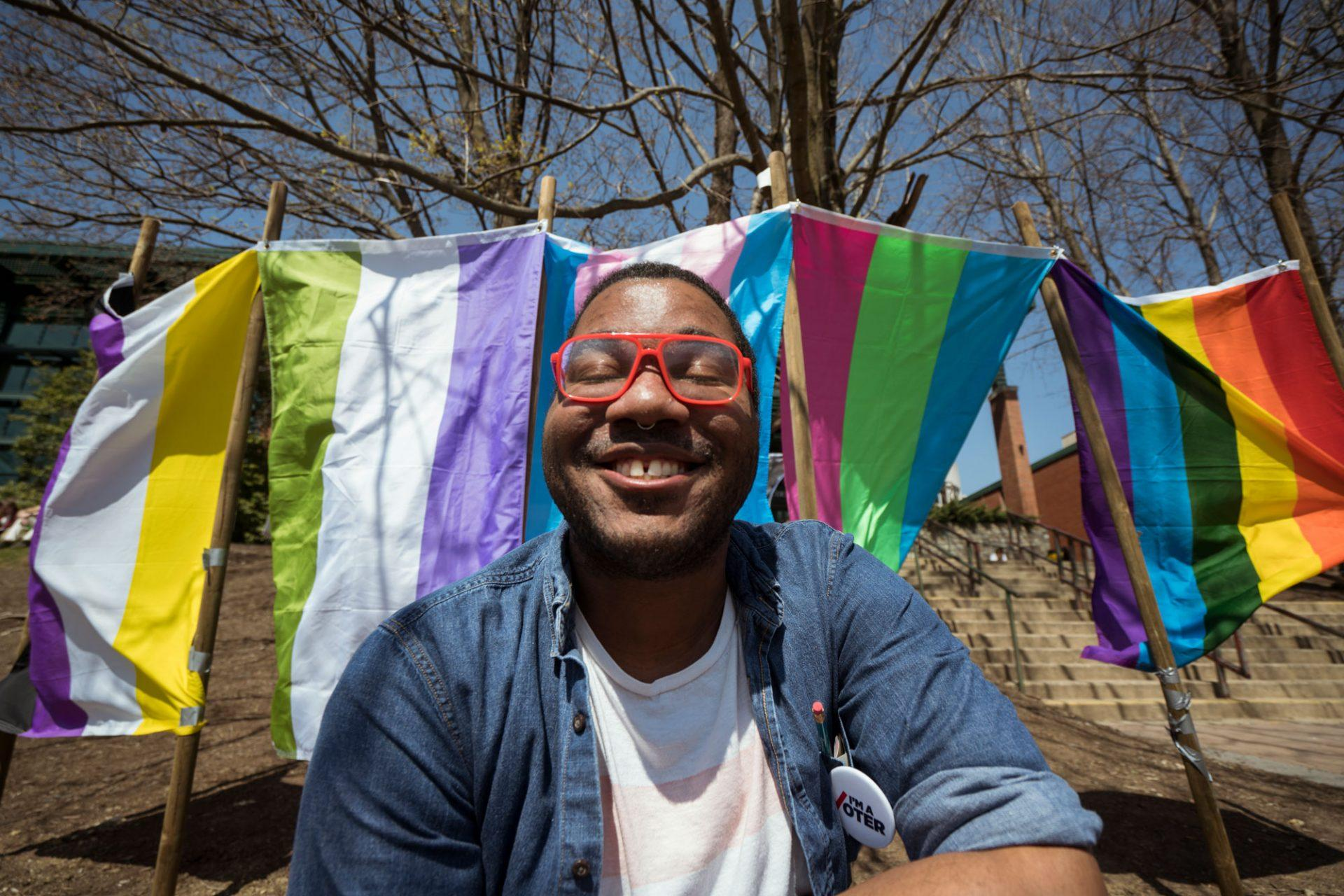 Senior Max Washington poses in front of the many flags of App State's Pride celebration.
