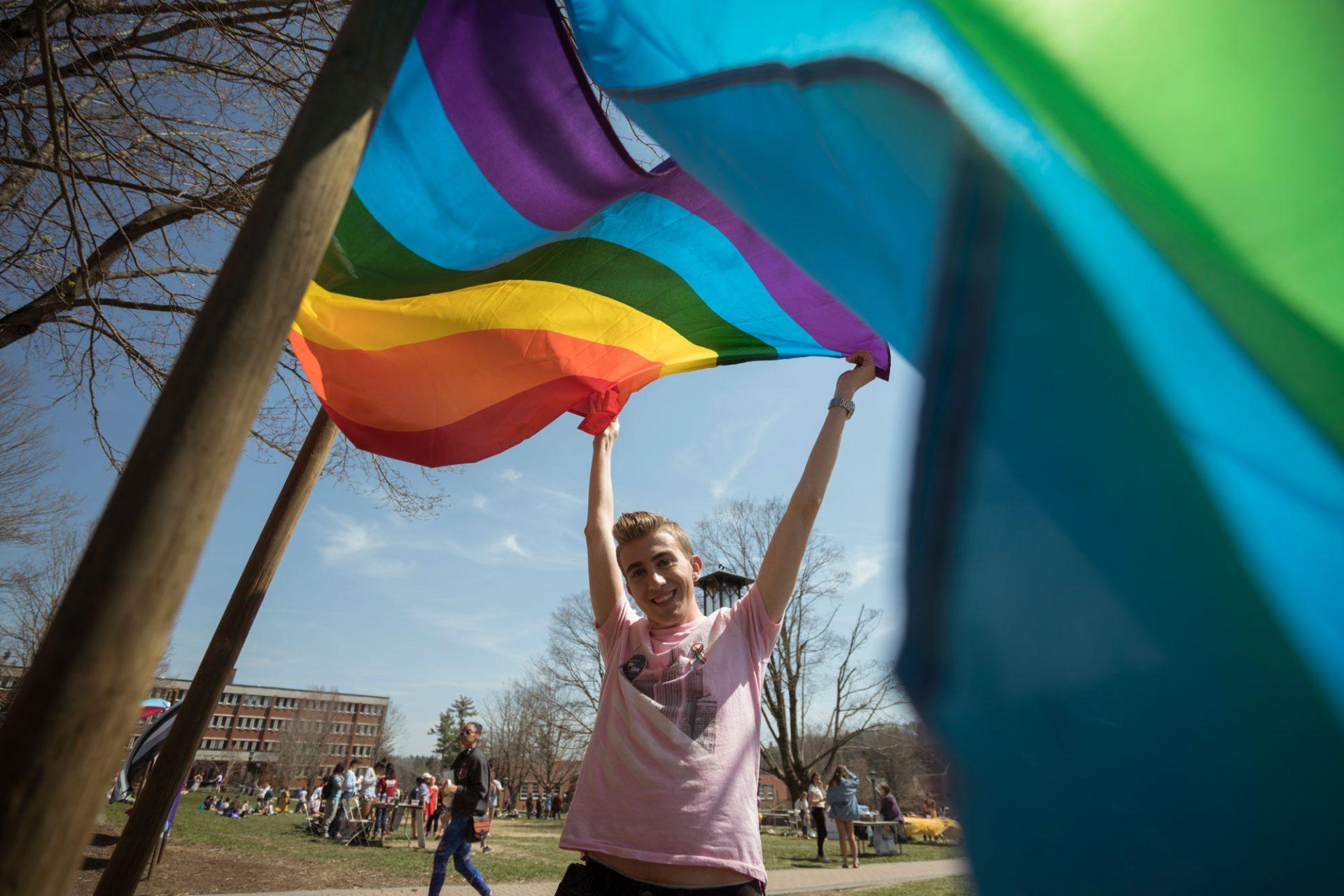 Scott Johnson waves the rainbow flag high on Sanford Mall.