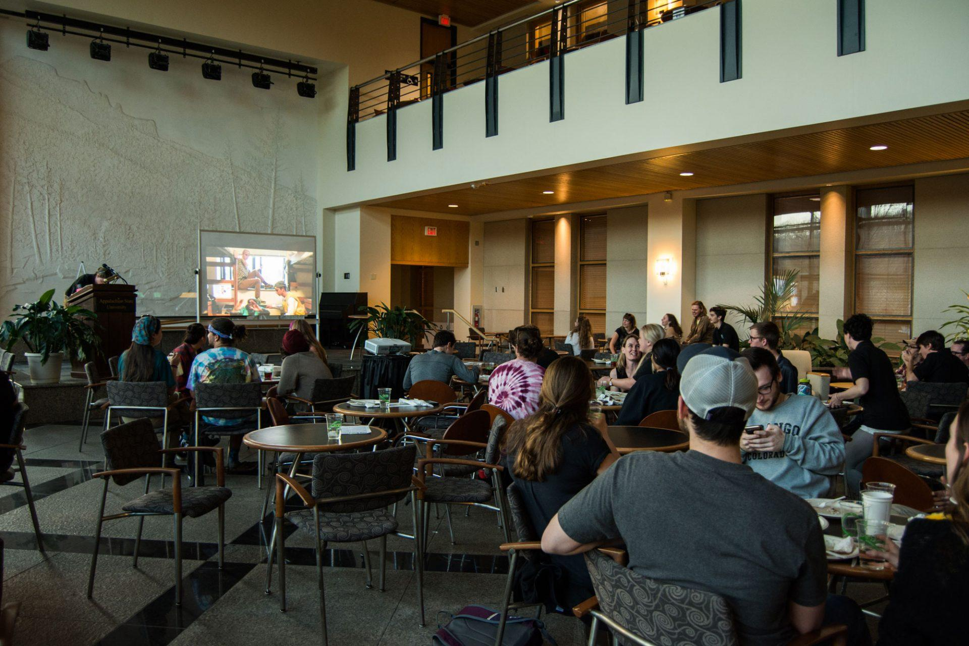 Students watch an informational video during the REI Forum on Thursday. The drop-in event offered a variety of free food and information.