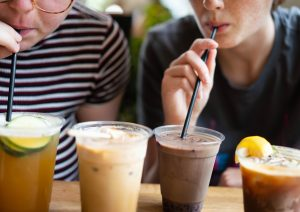 Two Hatchet Coffee patrons indulging the specialty iced drinks from their Summer Menu. The Menu features a vareity of chilled drinks with fruit and herb flavors, carbonated sodas and even spices.