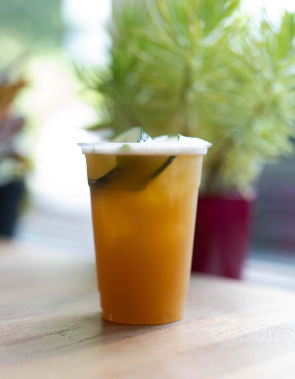 An iced Porch Swing, Hatchet Coffee's version of a summertime chai blended with peach nectar, cucumber and mint. One of four specialty drinks from their Summer Menu, Hatchet Coffee's Porch Swing is perfect for sipping while reading a good book.