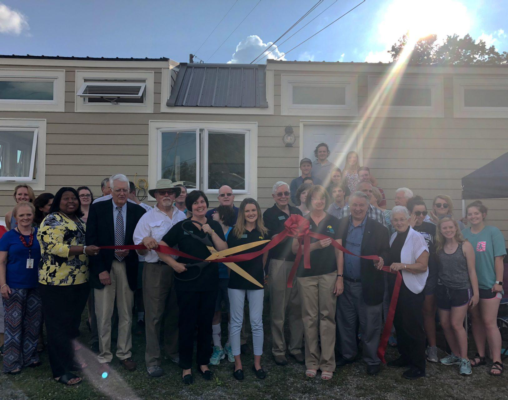 Surrounded+by+App+State+sustainable+technology+students%2C+Boone+politicians+and+community+members%2C+Vice+President+and+Director+of+Development+of+LIFE+Village%2C+Candace+Lang%2C+cuts+the+ribbon+for+a+new+tiny+house.+LIFE+Village+built+this+tiny+house+as+home+for+adults+with+autism+and+LIFE+team+members.+