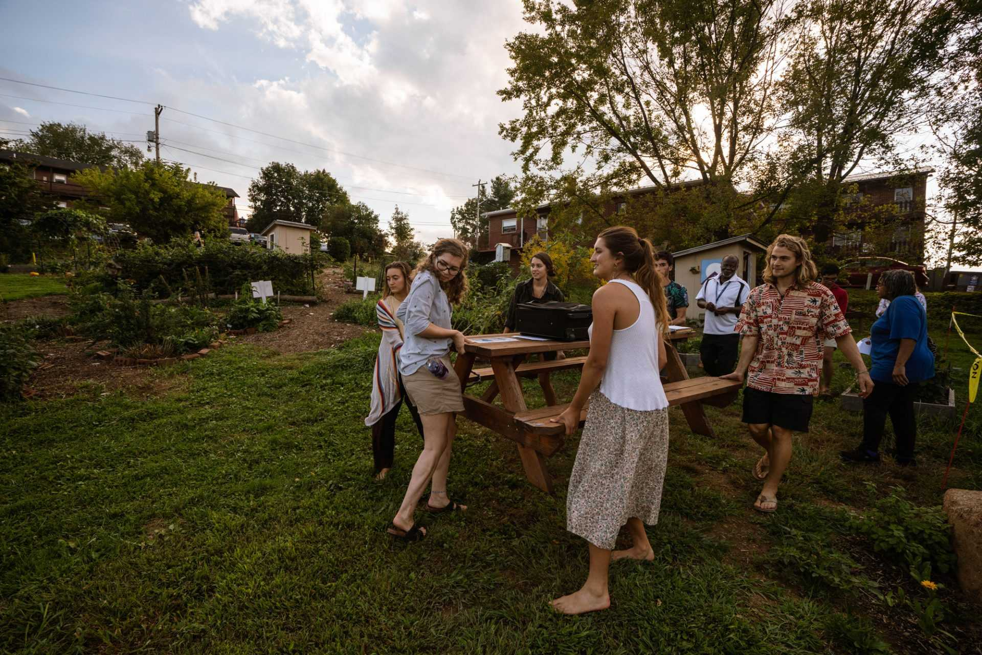 Sydney Blume, the campus garden coordinator, maneuvers a table downhill with a group of Sustainable Development majors.