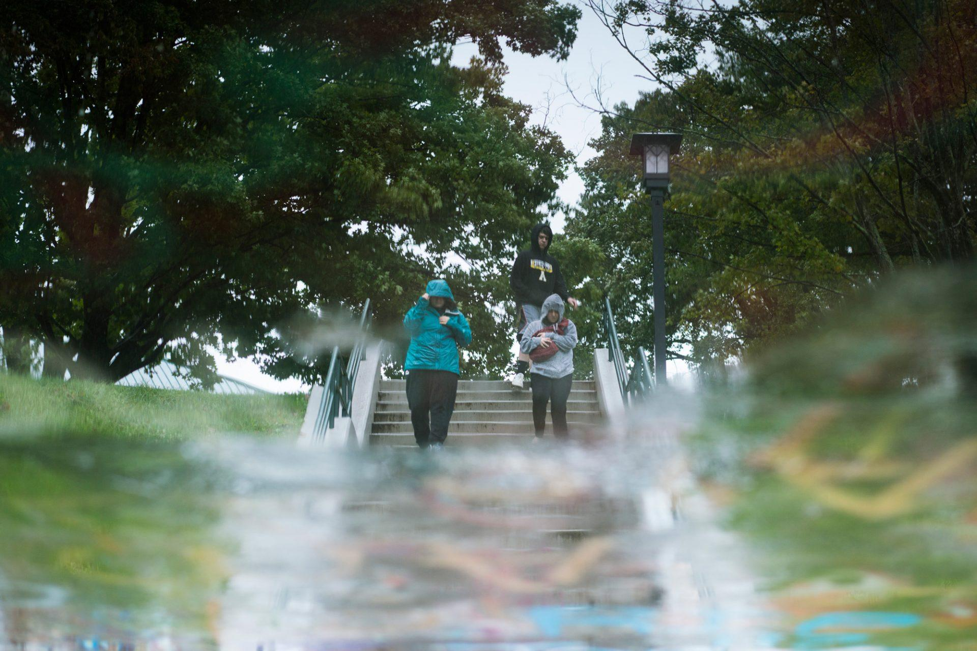 Students run from West campus to East campus despite the wind and rain.