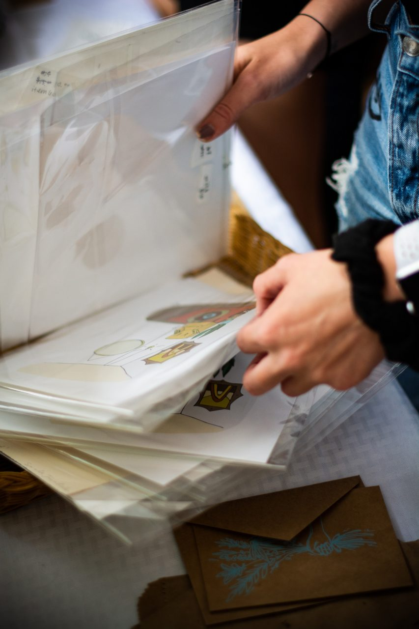 A customer flips through a heap of prints for sale at Pop Up Boone on Friday.