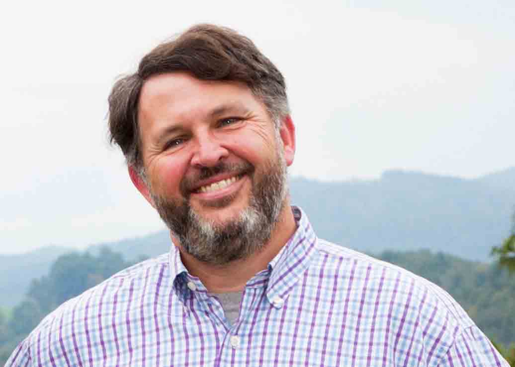 Democratic candidate for Watauga County Commissioner, Charlie Wallin, smiles in front of the scenic Blue Ridge Mountains.