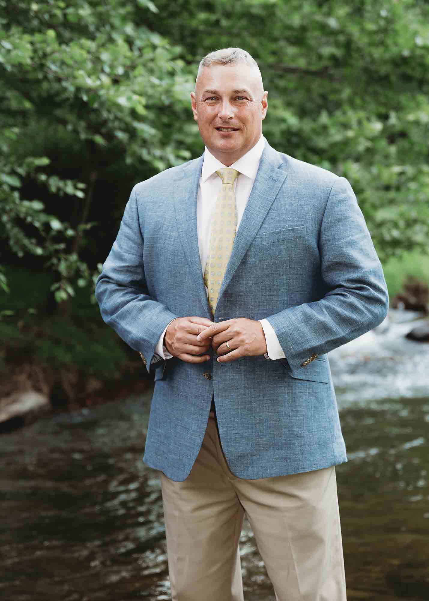 David Searcy, republican candiate for Watauga County Sheriff, poses in front of a flowing mountain river.
