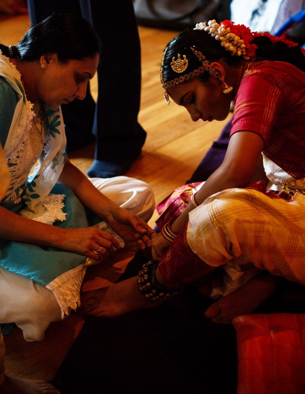 With help from her mother, Janavi Mehta straps bells to her ankles in preparation for her dance performance.