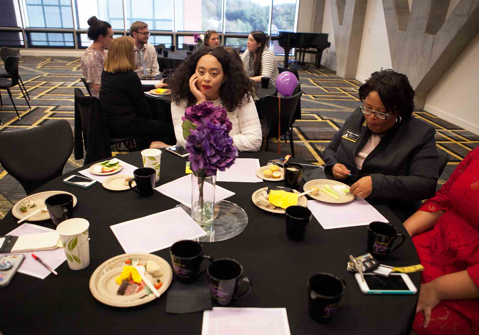 Kira Taylor (center), Danielle Carter (right) and others engage in conversation and indulge in afternoon tea treats at the 20th anniversary celebration of the Women's Center.