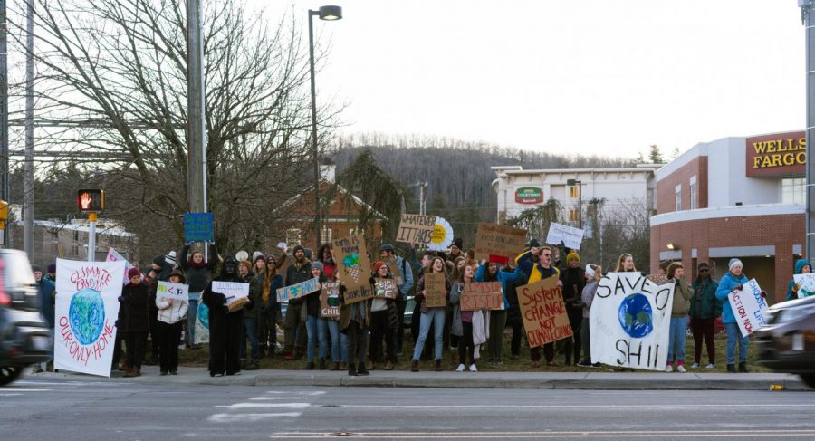 Members of the Climate Action Collaborative chant songs and hold sides during their parade on Blowing Rock Road toward Highway 105 January 19 .