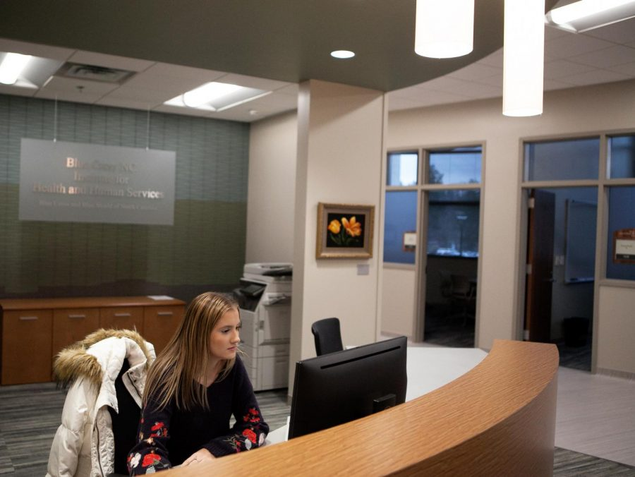 First year nutrition graduate student and graduate assistant of the Institute for Health and Human Services, Ashlyn Greene, works at her desk in the new IHHS clinic. The clinic is located in Leon Levine health sciences building. // Photo by Mickey Hutchings